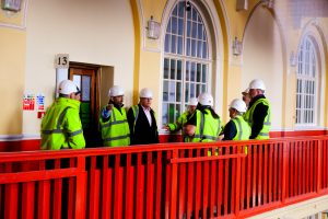 People in hard hats and PPE touring the Cambridge Road refurbishment site