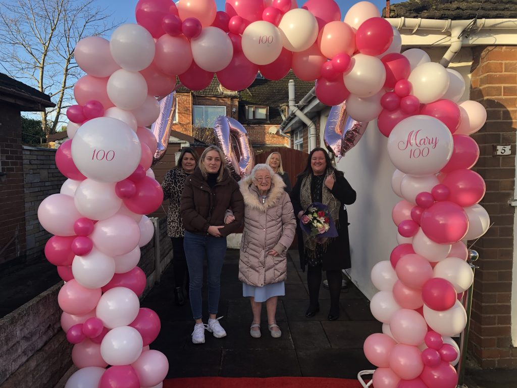 100 year old Mary with birthday balloons and birthday visitors