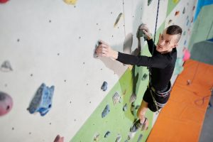 Image shows a man with limb difference climbing an indoor climbing wall.