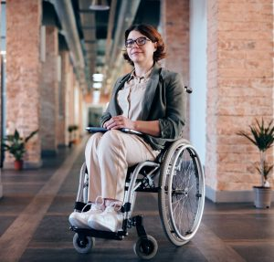 Image shows a woman smartly dressed in a wheelchair smiling at the camera.