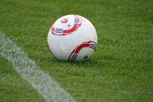 Football on a grass pitch near line markings