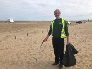 Green Sefton Ranger clearing litter along Sefton beaches