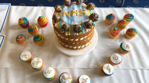 A layered sponge cake iced with 'NHS' surrounded by cup cakes spelling out he words 'Thank You'.