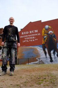 Paul Curtis next to his Red Rum mural in Southport, commissioned as part of Sefton's Borough of Culture celebrations for 2020.