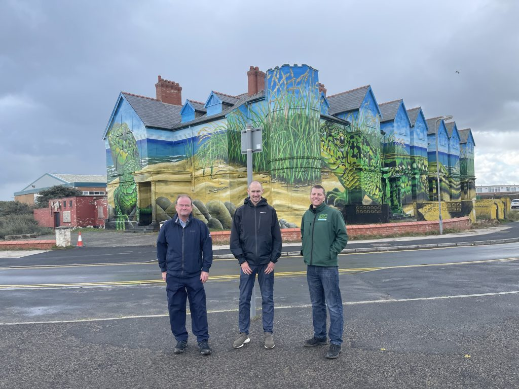 Cllr Ian Moncur, artist Paul Curtis and Green Sefton's Development Officer Andy Cutts stood in front of the sand lizard mural